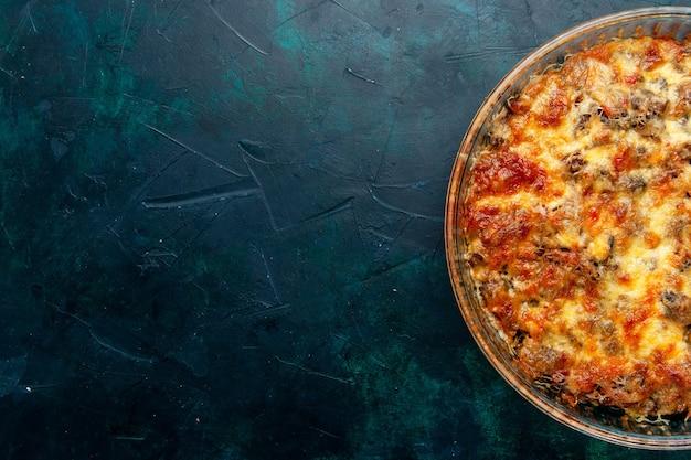 紺色の机の上にチーズと一緒に野菜とスライスした肉を使った上面図調理肉料理肉料理料理ディナーベイク