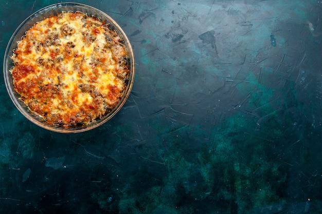 Вид сверху приготовленная мясная еда с овощами и нарезанным мясом вместе с сыром на темно-синем полу еда блюдо из мясной муки ужин в духовке