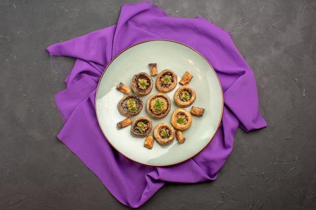 Vista dall'alto funghi cotti all'interno del piatto su un piatto di tessuto viola che cucina la cena dei funghi