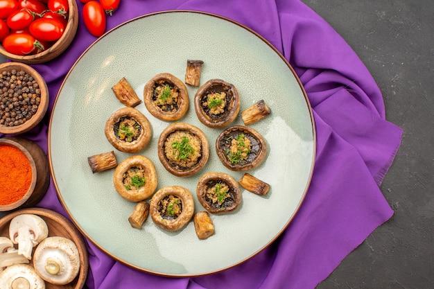 Vista dall'alto funghi cotti all'interno del piatto con condimenti sul piatto in tessuto viola che cucina la cena dei funghi