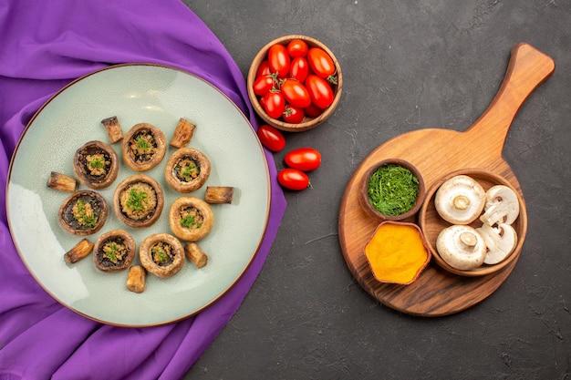 プレート内の調理済みキノコの上面図、トマトとグリーン、暗い表面の皿のキノコディナークッキングミール