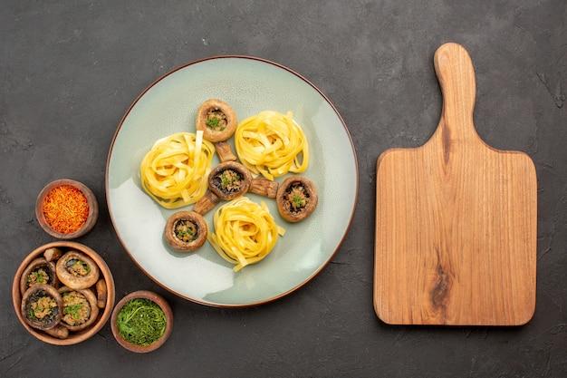Вид сверху приготовленные грибы с макаронами из теста на темном столе, жареная еда, ужин
