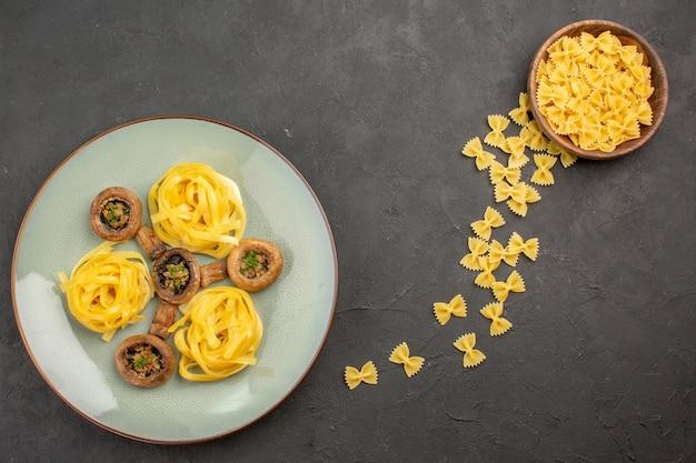 暗いテーブルのキノコの熟した野生の食事にパスタと一緒に調理されたキノコの上面図