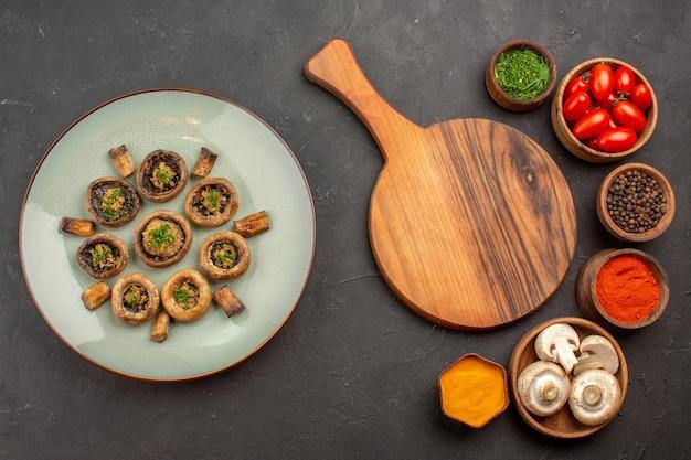 上面図調味料とトマトを使った調理済みキノコの暗い表面の料理の食事調理用キノコの夕食