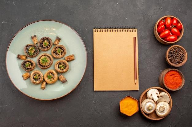 Вид сверху приготовленные грибы с приправами и помидорами на темном столе, приготовление ужина с грибами
