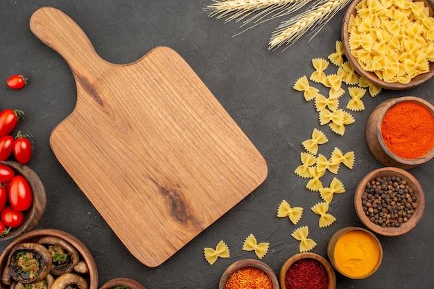 暗いテーブルのキノコの野生のパスタに調味料と一緒に調理されたキノコの上面図