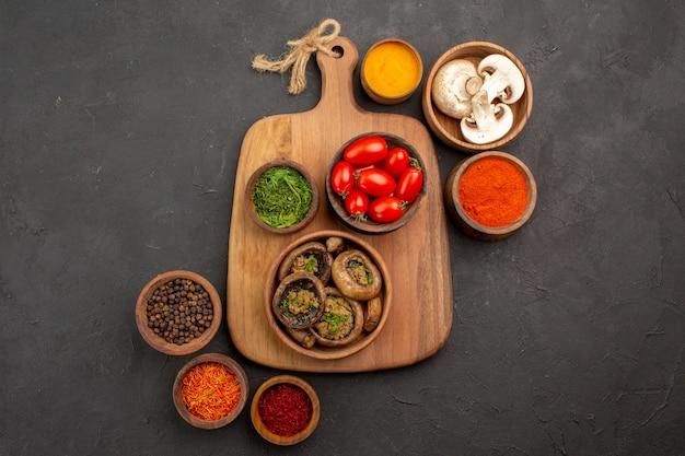 Вид сверху приготовленные грибы с приправами на темном столе спелые дикие продукты