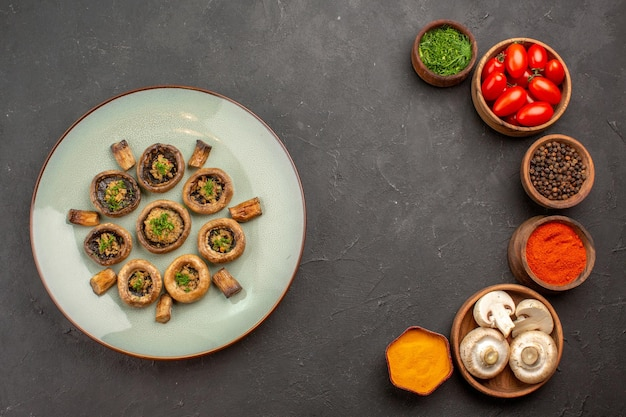 Vista dall'alto funghi cotti con condimenti e pomodori su un piatto di superficie scura che cucina la cena dei funghi
