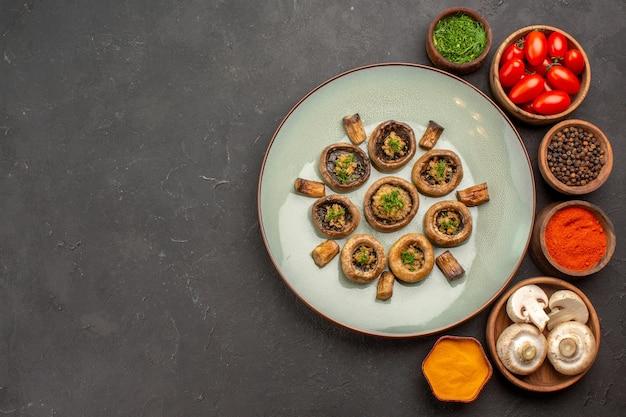 上面図トマトと調味料を使った調理済みキノコの暗い表面の料理の食事調理キノコの夕食
