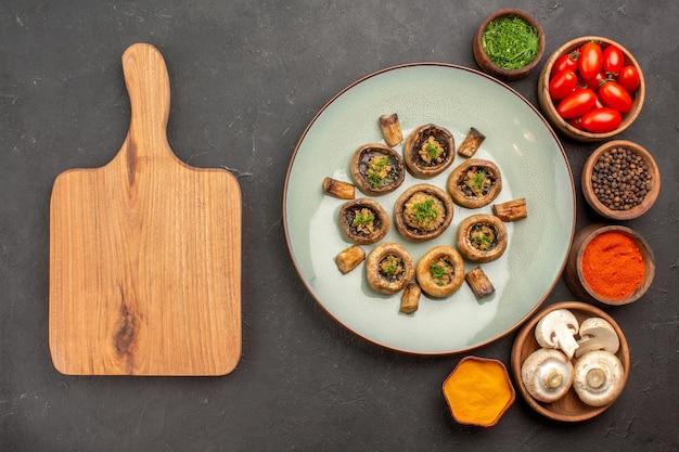Vista dall'alto funghi cotti con pomodori e condimenti sul piatto di superficie scura che cucina cena a base di funghi
