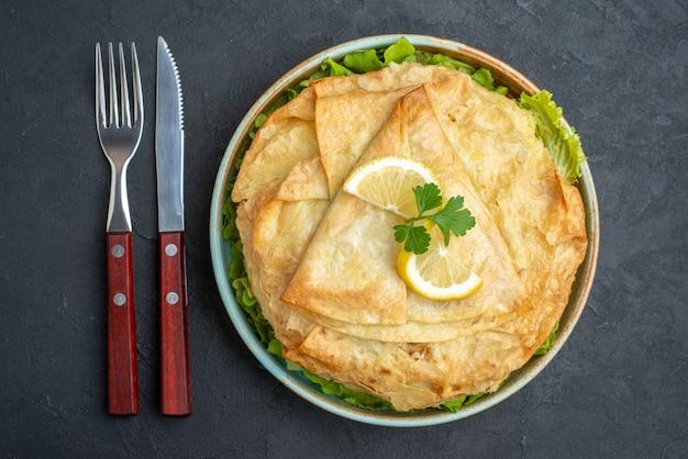 Vista dall'alto cotto pita all'interno del piatto con verdure e fette di limone sulla superficie scura