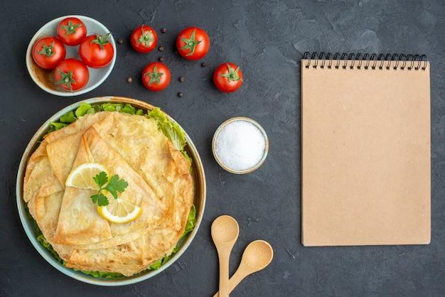 Vista dall'alto cotto pita all'interno del piatto con verdure, limone e pomodori sulla superficie scura