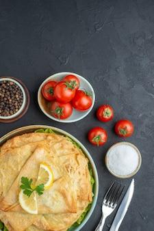 Vista dall'alto cotto pita all'interno del piatto con fette di limone e pomodori sulla superficie scura