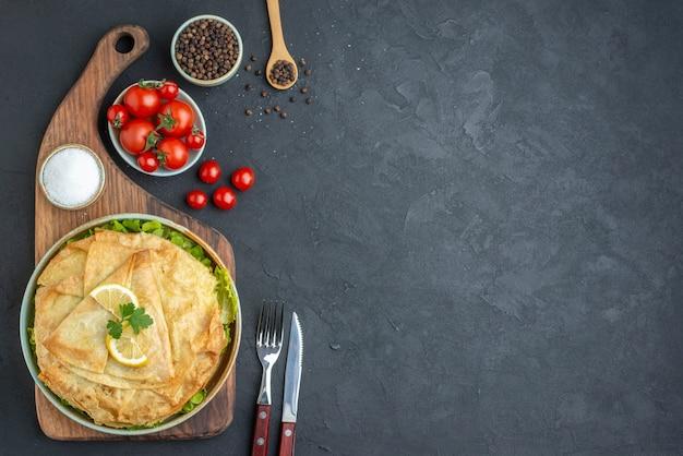 Vista dall'alto fette di pita cotte all'interno del piatto con il limone sulla superficie scura