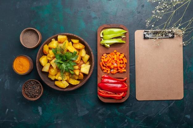 Vista dall'alto patate cotte con verdure insieme a condimenti e peperoni a fette sulla superficie blu scuro