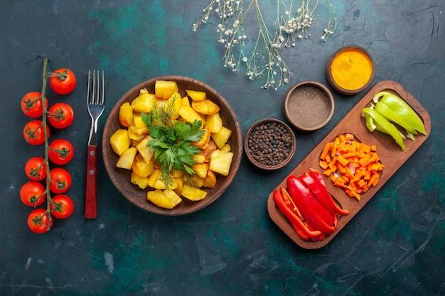 Vista dall'alto patate cotte con condimenti e peperoni a fette su superficie blu scuro