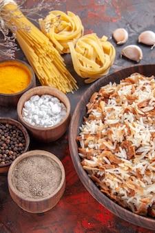 Vista dall'alto riso cotto insieme a condimenti sulla foto del piatto di cibo con superficie scura