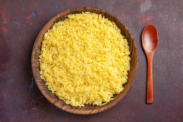 Vista dall'alto di riso cotto delizioso pasto all'interno del piatto marrone su uno spazio scuro