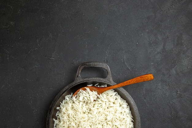Top view cooked rice inside pan on dark desk dinner meal food rice eastern