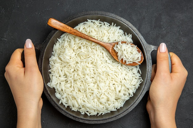 Top view cooked rice inside pan on the dark surface meal food rice eastern dinner