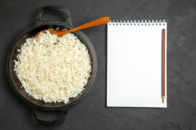 Vista dall'alto riso cotto all'interno della padella con blocco note sulla superficie scura cena cibo riso orientale