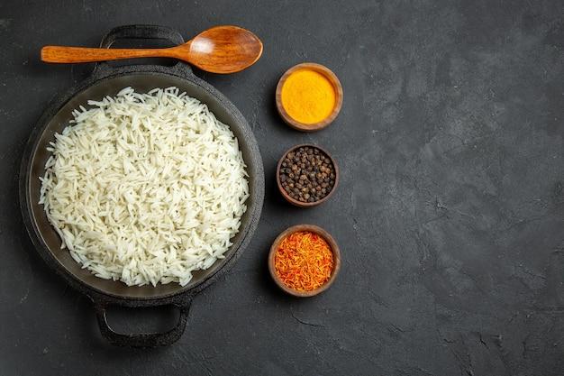 Vista dall'alto riso cotto all'interno della padella con condimenti sulla superficie scura pasto cibo cena orientale eastern