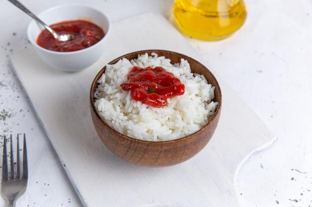 Vista dall'alto del gustoso pasto di riso cotto all'interno della pentola marrone con salsa piccante sulla cena del piatto di farina di riso sul pavimento bianco
