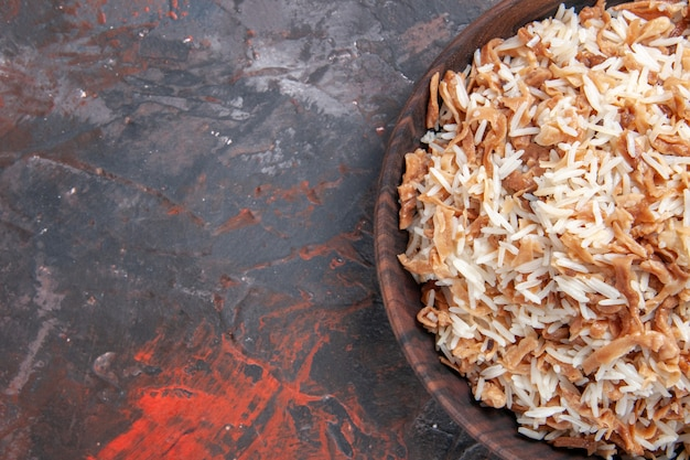 暗い表面の皿の食事の食糧パスタの生地のスライスが付いている上面図の炊飯米