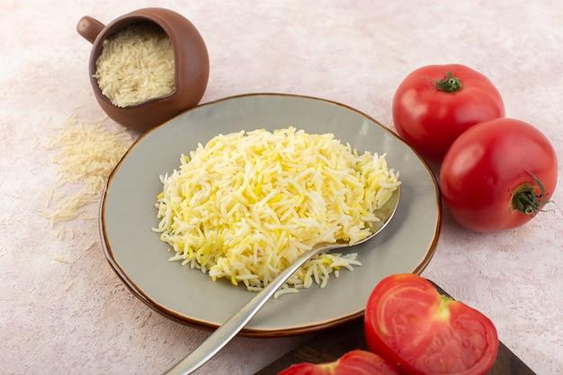 Una vista dall'alto ha cucinato il riso con i pomodori rossi freschi sul gusto di verdure del pasto dell'alimento dello scrittorio rosa