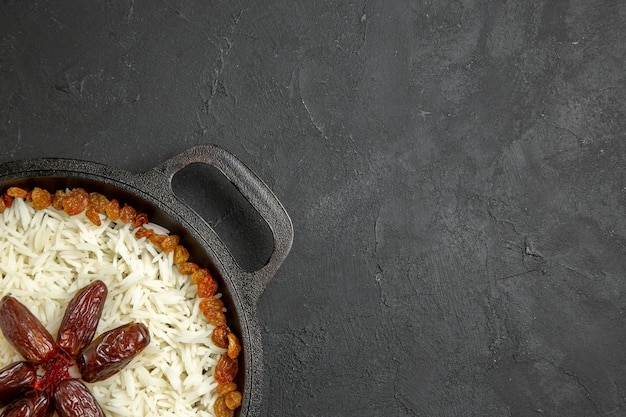 Top view cooked rice with raisins inside pan on dark grey surface meal food rice eastern dinner