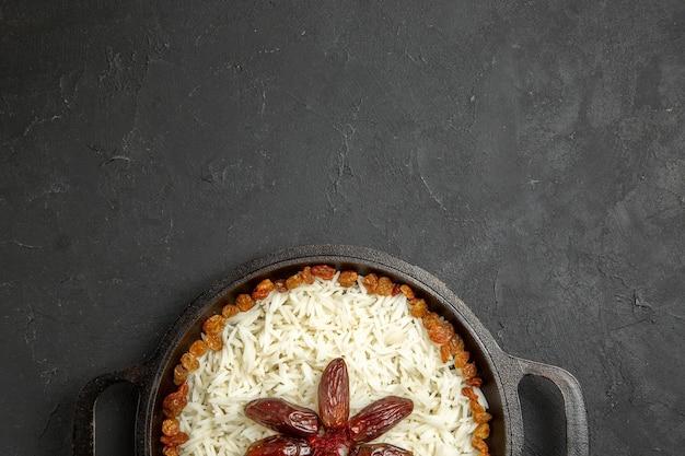 上面図暗い表面の食品米東部の食事の夕食の鍋の中にレーズンとご飯
