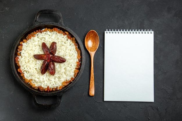 濃い表面の食事に調味料とレーズンを添えた上面図ご飯