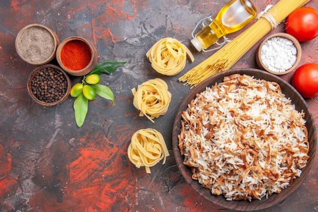 Vista dall'alto riso cotto con condimenti sulla foto del pasto scuro del piatto di cibo di superficie scura