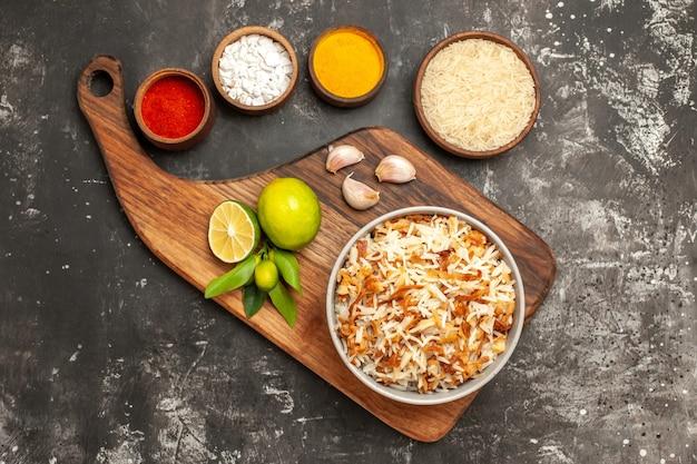 Вид сверху приготовленный рис с приправами на темной поверхности блюдо из темной пищевой специи
