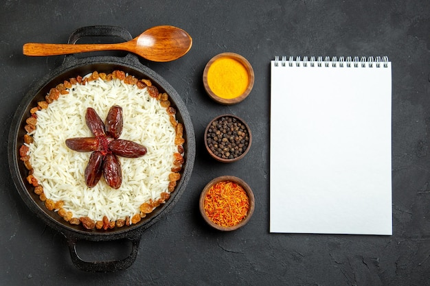 Top view cooked rice with seasonings and raisins on dark surface meal food rice eastern dinner