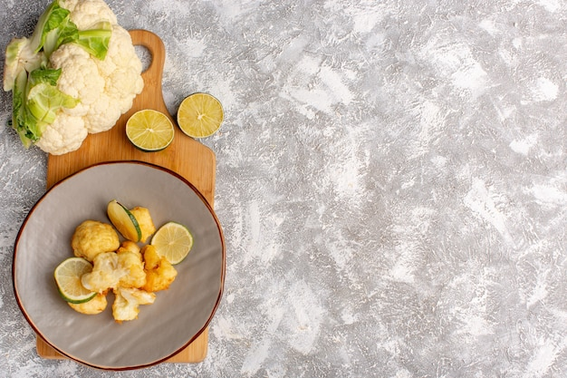 Top view of cooked sliced cauliflower inside plate with lemon on light-white surface