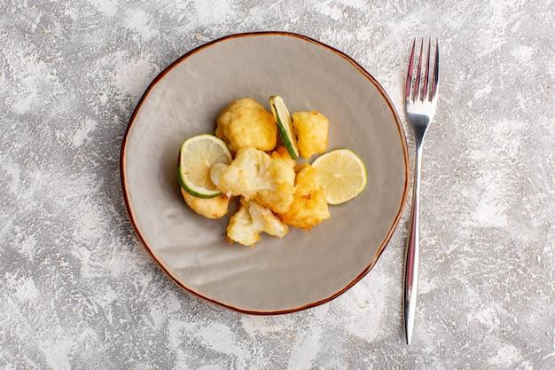 Vista dall'alto del cavolfiore affettato cotto all'interno della piastra con il limone sulla superficie bianca chiara