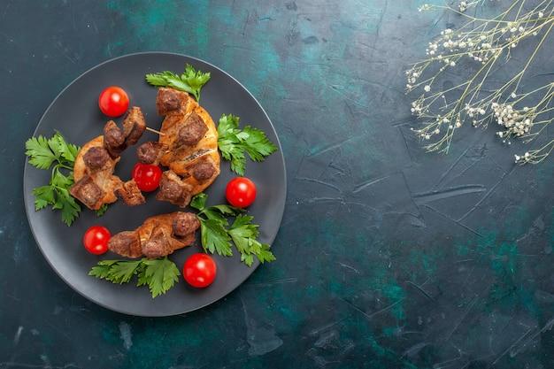 Вид сверху приготовленное нарезанное мясо с зеленью и красными помидорами черри на темно-синем столе