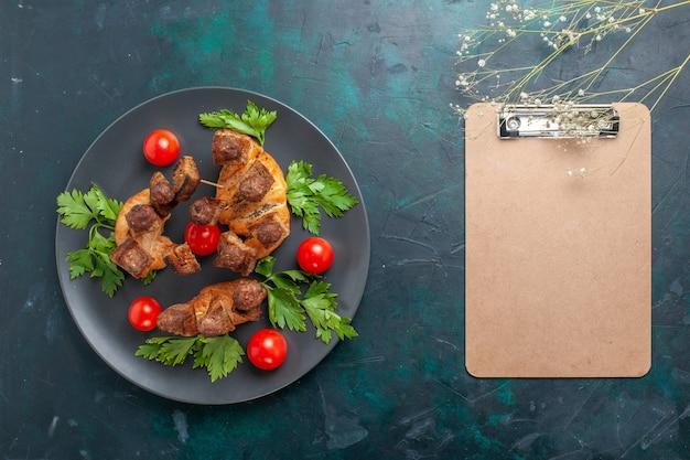 Вид сверху приготовленное нарезанное мясо с зеленью и красными помидорами черри на темно-синей поверхности
