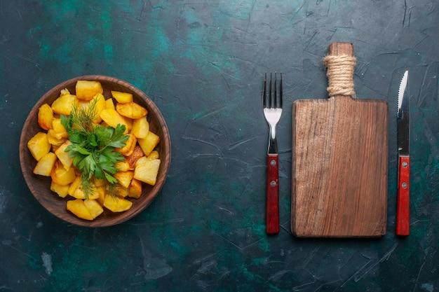 진한 파란색 책상에 갈색 접시 안에 채소와 함께 상위 뷰 요리 슬라이스 감자 맛있는 식사