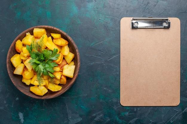 Vista dall'alto cotte patate a fette delizioso pasto con verdure all'interno del piatto marrone con blocco note sulla scrivania blu scuro
