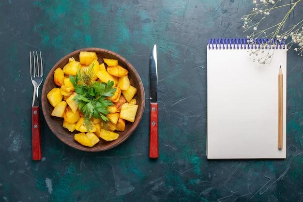 Vista dall'alto cotte patate a fette delizioso pasto con verdure con blocco note sulla scrivania blu scuro