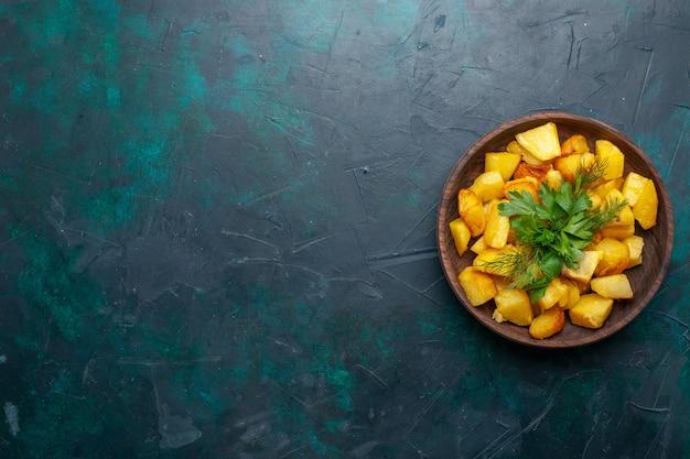 紺色の表面の茶色のプレートの内側に緑のある調理済みスライスポテトの上面図