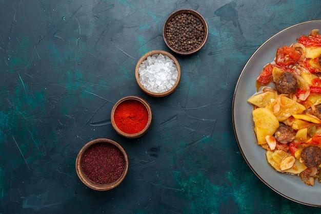 진한 파란색 책상에 조미료와 함께 미트볼과 함께 썰어 진 감자를 요리 한 상위 뷰.