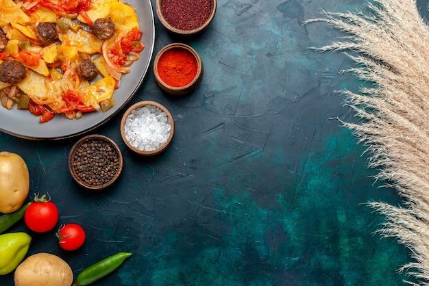 Vista dall'alto di patate affettate cotte con polpette di carne e verdure cotte sulla scrivania blu scuro.