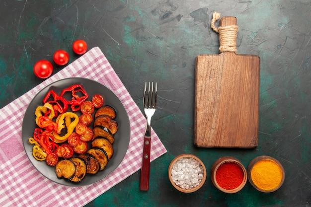 Вид сверху приготовленные нарезанные овощи болгарский перец и баклажаны с приправами на зеленой поверхности