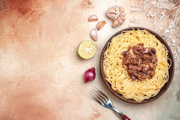 Spaghetti cucinati vista dall'alto con carne macinata su un piatto di pasta a base di carne di pasta piano chiaro