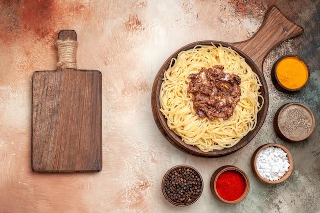 Spaghetti cucinati vista dall'alto con carne macinata su un piatto leggero di pasta a base di carne