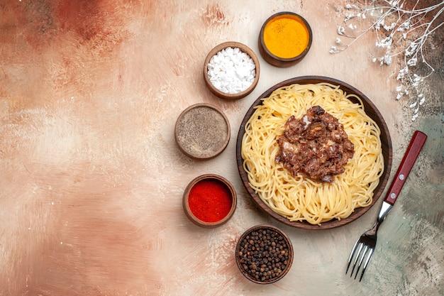 Spaghetti cucinati vista dall'alto con carne macinata su carne leggera da tavola