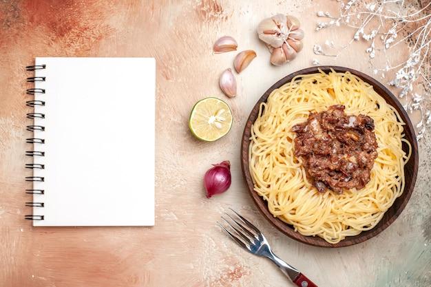Vista dall'alto spaghetti cotti con carne macinata su tavola leggera pasta piatto di pasta a base di carne
